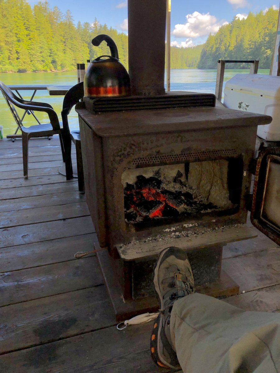 Enjoying a warm fire while waiting for my meal at The Crab Shack Nitinaht Narrows on the West Coast Trail