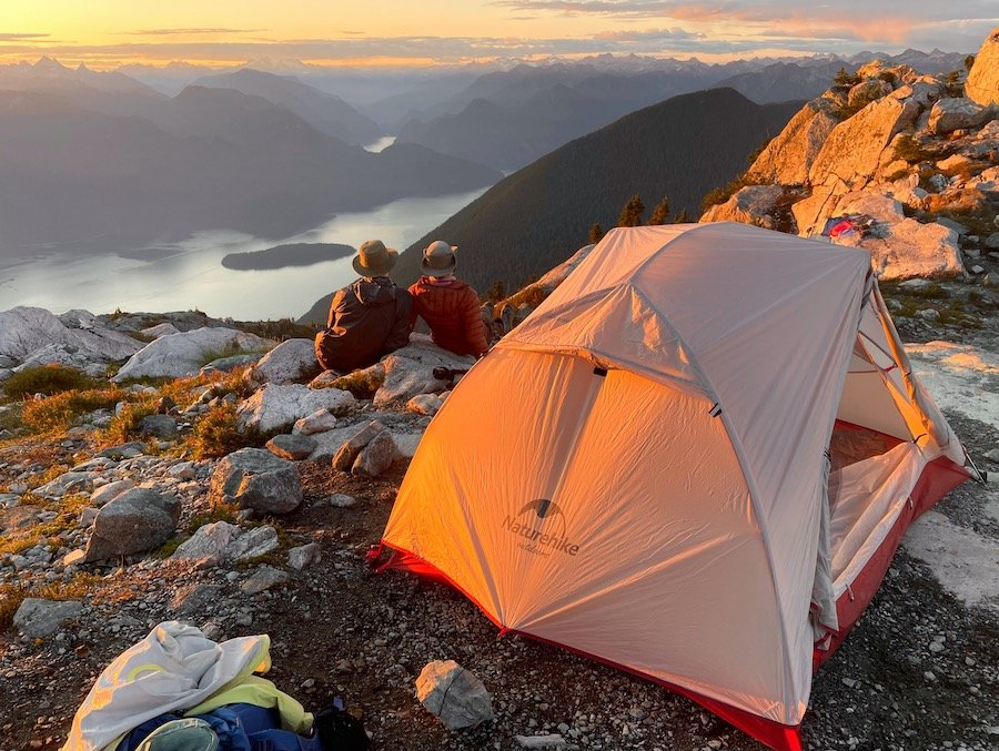 Couple watching sun set by tent on Panorama Ridge Golden Ears Provincial Park