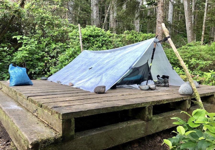 Tarp and bivy set-up using rocks and branches at Laura Creek, North Coast Trail